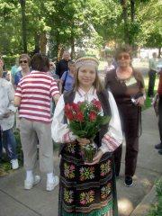 Dressed in traditional Lithuanian costume, Kourtney Baker holds roses that she will give to participants to commemorate loved ones at the dedication ceremony.