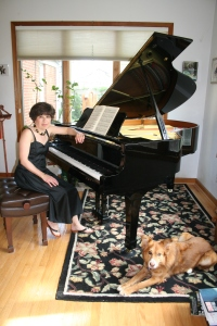 Paulette George with her Yamaha grand piano and Ellie the retriever