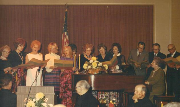 Members of the renowned church choir sing at the retirement party for long-time pastor the Rev. S.O. Yunker at the Springfield Elks Club Nov. 14, 1971. Left to right: unidentifed person, Mary Ann Foster, Ann (Pazametsky) Traeger, unidentified person, Mary Ann Rackauskas, Bernice Kurila, Catherine (Gillette) Cooper, unidentified  woman, Peter Urbanckas, Alfred Urbanckas, Charlie Foster, Walter Rodutskey (off the right edge of the photo), and Anne (Mosteika) Foster playing the piano.
