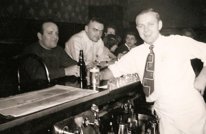 Tony Yuscius serving Joe Saputo in dark sweater, according to Sandra Coffee. Joe and his brother Frank  operated Saputo Twins Corner downtown.