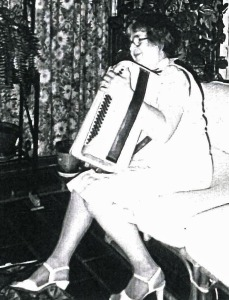 Josephine (Kohlrus) Baksys playing son-in-law Jay Wheeler's accordion, 1984, Courtland, Calif.